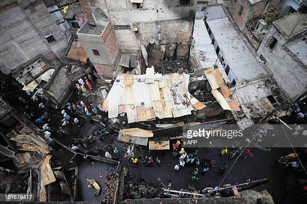 Bangladeshi pedestrians walk past the site of the Old Dhaka fire in Dhaka on June 5 2010 The national flag flew at halfmast and people of all faiths...