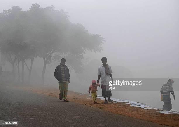 Bangladeshi pedestrians walk through winter morning fog in Dhaka on December 13 2009 AFP PHOTO/Munir uz ZAMAN
