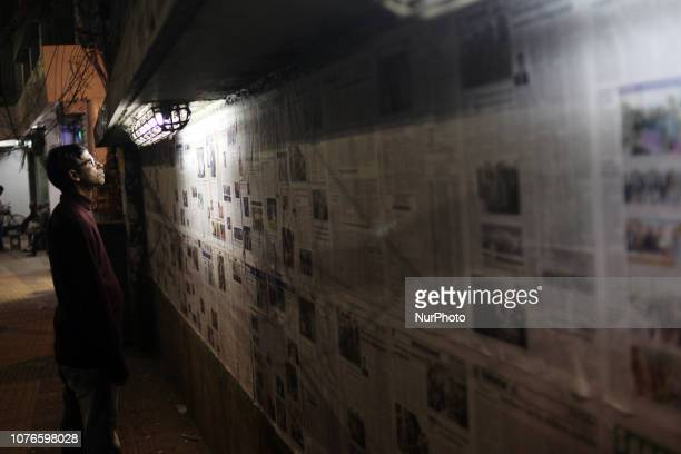 Bangladeshi people are reading wall held newspaper after the day of country's 11th national general election A crushing victory for an election over...