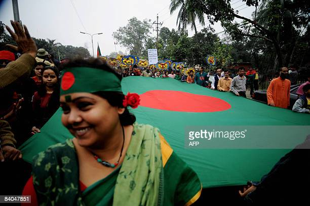 Bangladeshi people carry agiant national flag during a rally held to mark country's 37th Victory Day in Dhaka on December 16 2008 Bangladesh won...