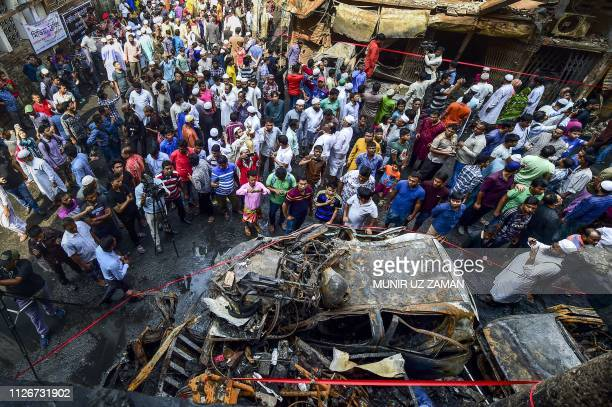 TOPSHOT Bangladeshi people gather around the wreckage of cars that burnt in a fire in Dhaka Bangladesh's capital city on February 22 2019 Funerals...