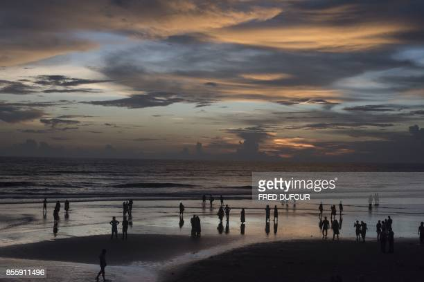 Bangladeshi people gather on the shore to look at the sunset on Inani beach near Cox's Bazar on September 30 2017 More than 2000 Rohingya have massed...