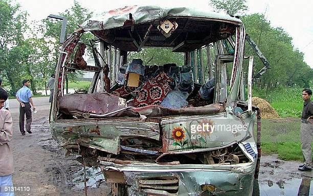 Bangladeshi people gather to look at the wreckage of a bus following a road accident in Chittagong 16 September 2004 Twentysix people were killed and...