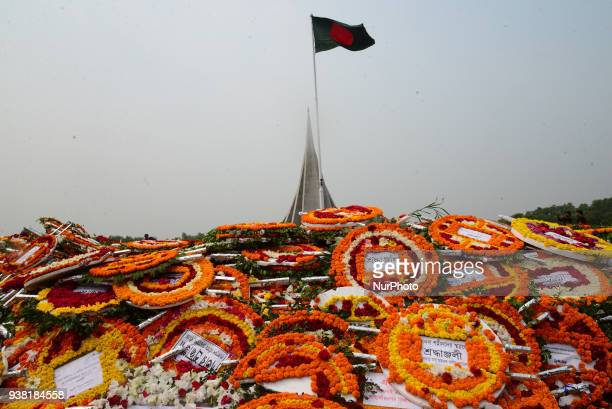 Bangladeshi people gather with flags and flowers to show their respect during the celebration of the country's Independence Day at the National...