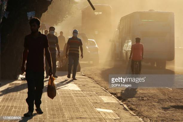 Bangladeshi people walk in a polluted air environment. A study says, Air pollution shortens life expectancy by seven years in Bangladesh.
