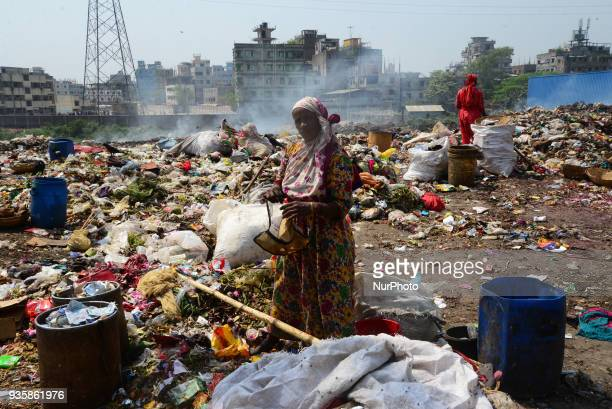 Bangladeshi people waste picker picks the non biodegradable waste to be used for the recycling industry in waste Dump Yard in Dhaka Bangladesh on...