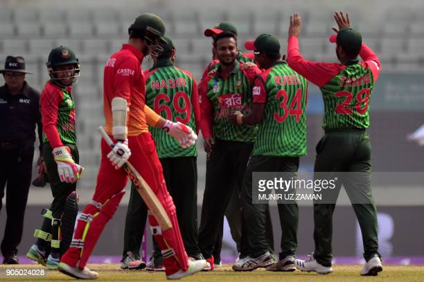 Bangladeshi players congratulate teammate Shakib Al Hasan after the dismissal of Zimbabwe's Craig Ervine during the first One Day International...