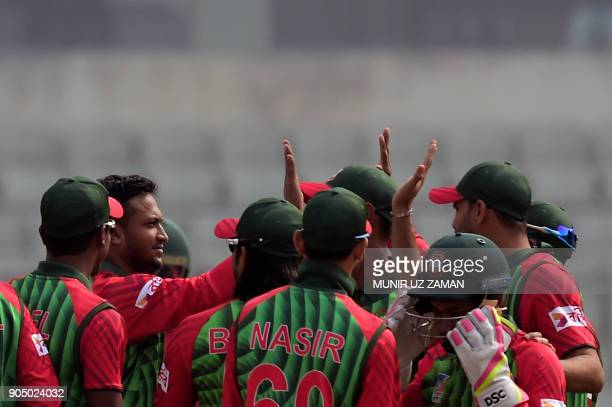 Bangladeshi players congratulate teammate Shakib Al Hasan after the dismissal of Zimbabwe's Solomon Mire during the first One Day International...