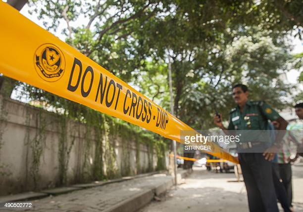 Bangladeshi police officers stand guard at the site where an Italian charity worker was shot to death by attackers in Dhaka on September 29 2015...