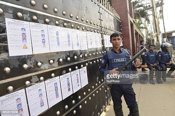 Bangladeshi police personnel stand guard in front of a shut garments factory at Ashulia outskirts of Dhaka Bangladesh on December 21 2016 A total of...