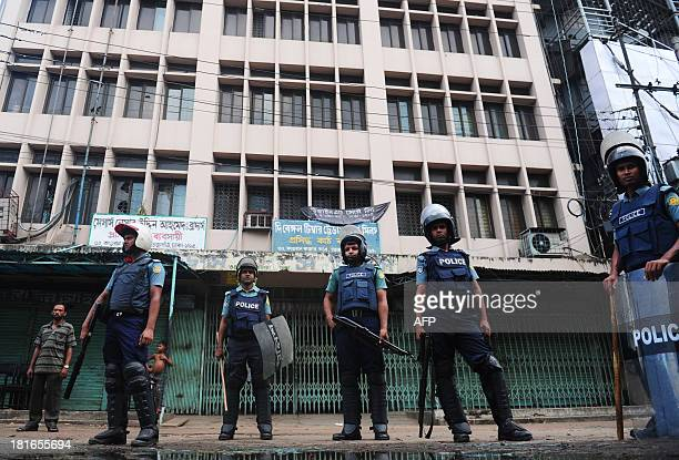 Bangladeshi police stand guard in front of a closed garment factory in Dhaka on September 23 2013 Angry Bangladeshi garment workers blocked roads set...
