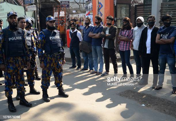 TOPSHOT Bangladeshi police stand guard next to leftwing activists organised by the Communist Party of Bangladesh wearing black cloth over their...
