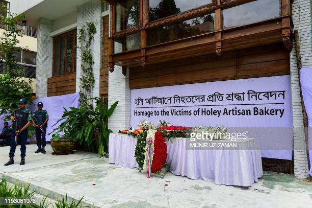 Bangladeshi police stand guard next to the tribute to victims of the Holey Artisan Bakery cafe siege to commemorate the third anniversary of the...