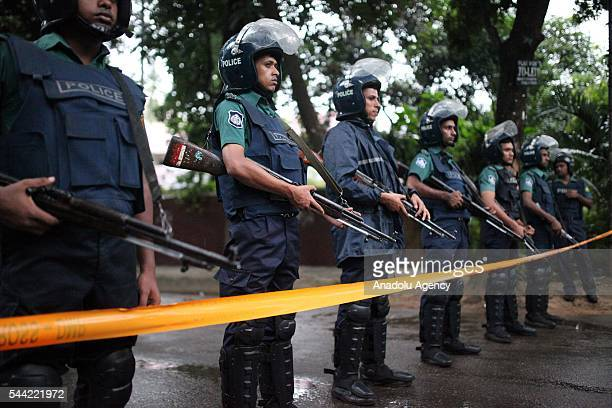 Bangladeshi police stand guard outside the Holey Artisan Bakery cafe currently under a hostage siege by armed gunmen in Dhaka Bangladesh on July 02...