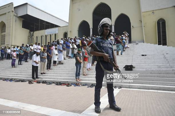 A Bangladeshi police stands guard after two mosques have been attacked in New Zealand as Muslims offer Friday prayers in Dhaka on March 15 2019...