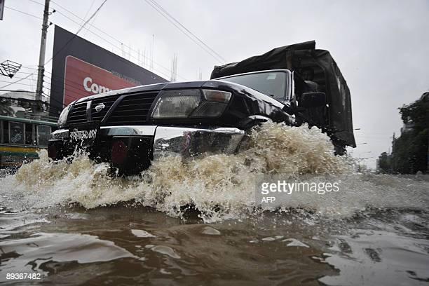 A Bangladeshi police truck drives through flood waters in the Bangladeshi capital of Dhaka on July 28 2009 Seasonal monsoon rains brought Dhaka to a...