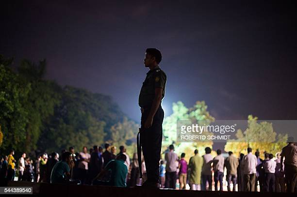 Bangladeshi policeman keeps guard near a group of peace activists who had come together to sing and light candles in a park following an attack and...