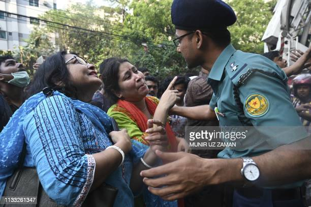 A Bangladeshi policeman speaks with two women whose relative was believed to be stuck inside a burning office building in Dhaka on March 28 2019 A...