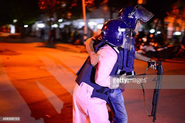Bangladeshi policeman that was injured during an attack on an upscale restaurant is helped by a colleague in Dhaka on July 1 2016 Heavily armed...