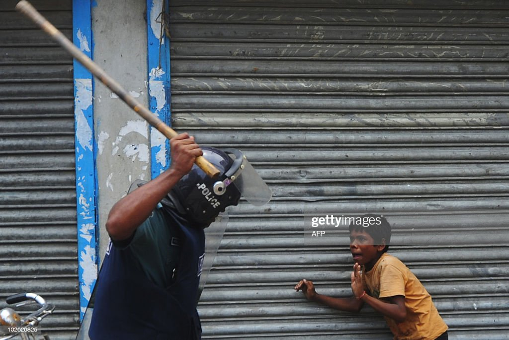 A Bangladeshi policeman threatens a chil : News Photo