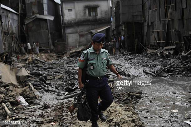 A Bangladeshi policeman walks on the site of a collapsed fourstorey building in Dhaka on June 3 2010 The death toll from the building collapse in the...
