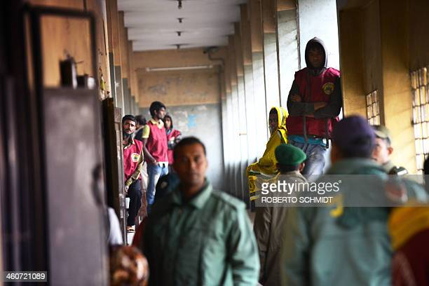 Bangladeshi policemen and polling station security monitors and Bangladeshi policemen stand at an otherwisedeserted polling station in Dhaka on...