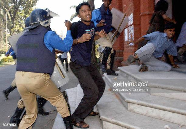 Bangladeshi policemen hold students as they disperse a demonstration in Dhaka 03 March 2004 Batonwielding police fired tear gas to break up the...
