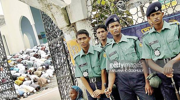 Bangladeshi policemen stand guard outside the Baitul Mukarram mosque during Friday prayers in Dhaka 19 August 2005 A Bangladesh madrassa student...
