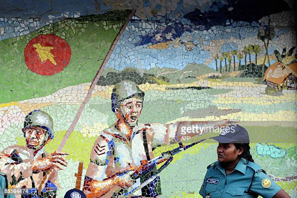A Bangladeshi policewoman stands beside a mural depicting the Bangaldesh Rifles in Dhaka on March 1 2009 Bangladeshi police were hunting for more...