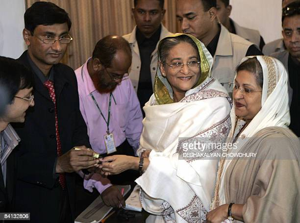 A Bangladeshi polling officer puts an ink mark on the finger of former Bangladeshi Prime Minister and leader of The Awami League party Sheikh Hasina...