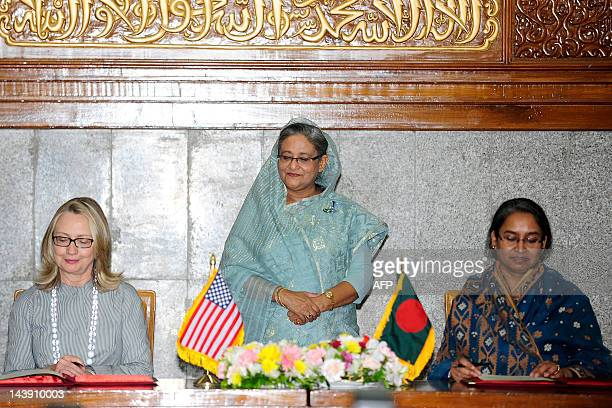 Bangladeshi prime minister Sheikh Hasina looks on as US Secretary of State Hillary Rodham Clinton and Bangladesh Foreign Minster Dipu Moni signi an...
