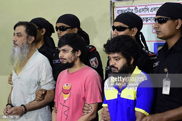 Bangladeshi Rapid Action Battalion personnel accompany suspects Touhidur Rahman Sadek Ali and Aminul Mallick who have been arrested for the murder of...