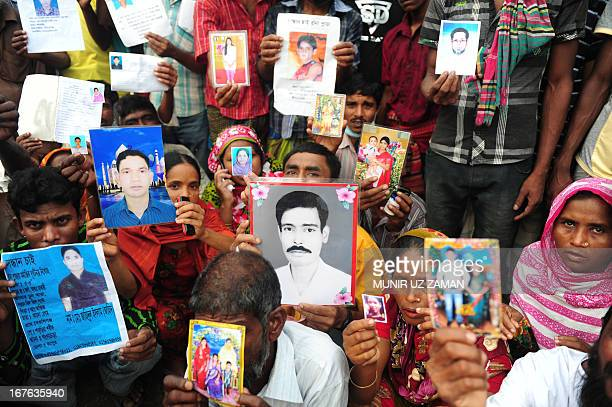 Bangladeshi relatives hold photos of the missing and dead workers three days after an eightstorey building collapsed in Savar on the outskirts of...