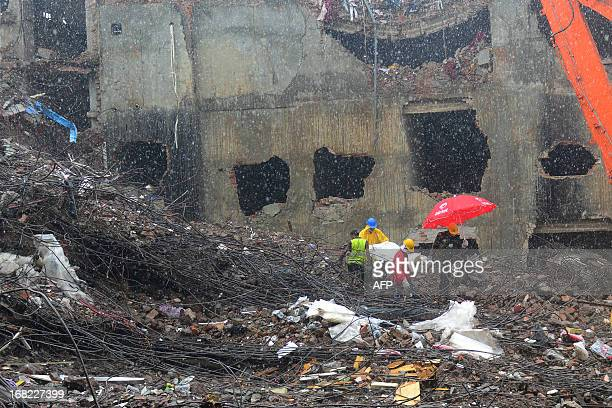 Bangladeshi rescue personnel carry stretchers with the remains of garment workers from the site of a collapsed building as heavy machinery clear the...