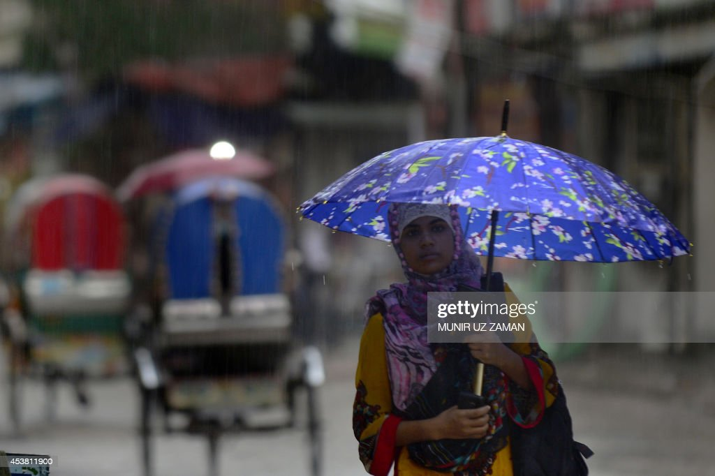A Bangladeshi resident walks along a road during heavy rain in Dhaka on August 19, 2014. Seven rivers in Bangladesh are flowing above the danger mark after heavy rains. AFP PHOTO/Munir uz ZAMAN