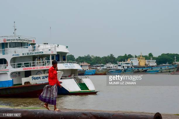 A Bangladeshi resident walks past cargo and tourist boats moored along the Rupsha river in Khulna on May 3 as Cyclone Fani barrels northeastwards...