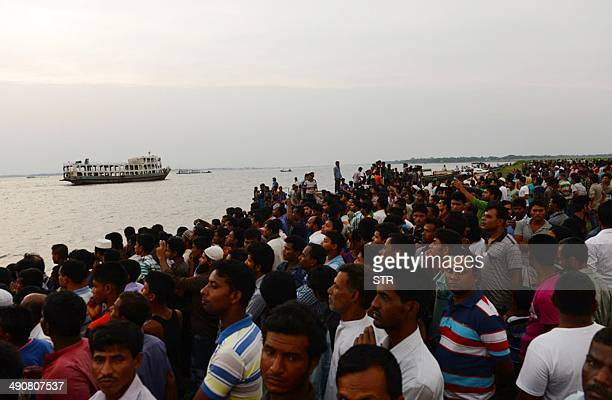 Bangladeshi residents gather near to the site where a ferry capsized and sank in bad weather on the river Meghna in Munshiganj district some 50...