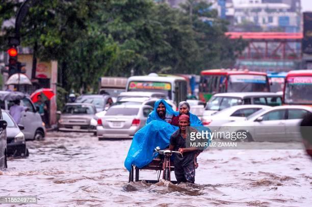 A Bangladeshi rickshaw puller makes his way through heavy rainfall at a waterlogged street during the monsoon season in Dhaka on July 12 2019
