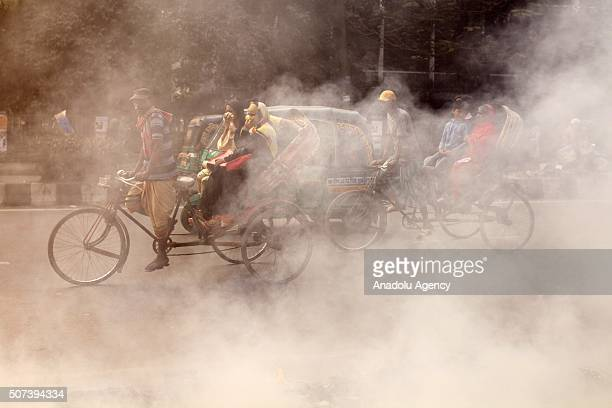 Bangladeshi rickshaw puller rides past smokes created by burning waste materials on a street in Dhaka Bangladesh on January 29 2016 The High Court on...