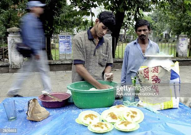 Bangladeshi roadside vendor prepares a traditional Bangladeshi cake known locally asBhapa Pittha in front of Dhaka university 22 December 2003 as a...