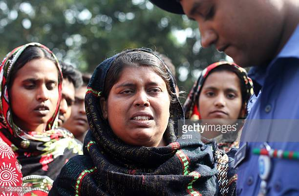 Bangladeshi Sabiha Khatun speaks to police about her missing younger sister who was a worker in a garment factory that burned the day before in...
