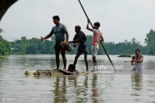 TOPSHOT Bangladeshi sail on a raft made of banana tree trunks in an area submerged by flood in Kurigram northern Bangladesh on August 14 2017 At...