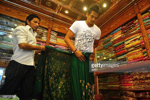 A Bangladeshi salesman displays saris at a textile shop during the Islamic holy month of Ramadan in Dhaka on August 30 2010 Ramadan is the Muslim...