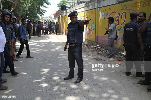 Bangladeshi security forces stand guard in front of a home after three suspected militants have been killed during a gunfight at a militant hideout...