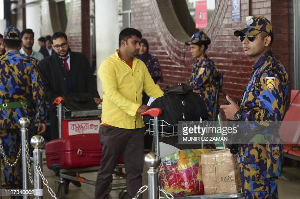 Bangladeshi security personnel stand guard in a passenger's entrance of the Hazrat Shahjalal International Airport in Dhaka on February 25 as...