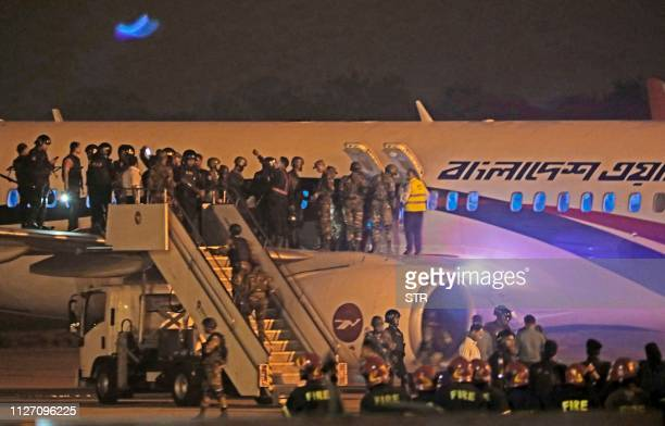 Bangladeshi security personnel stand guard near a Dubaibound Bangladesh Biman plane on the tarmac of the Shah Amanat International Airport in...