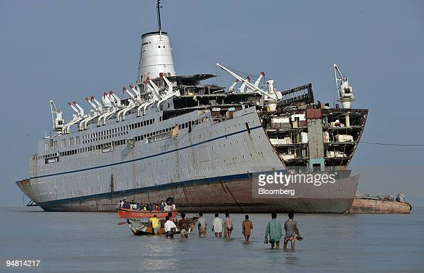 Bangladeshi shipbreakers wade out to waiting launches on their way to demolish a beached cruise ship April 30 2005 at a yard near Chittagong Scrapped...
