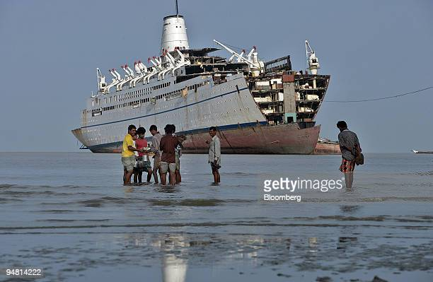 Bangladeshi shipbreakers wait for their transport on the way to demolish a beached cruise ship April 30 2005 at a yard near Chittagong Scrapped ships...