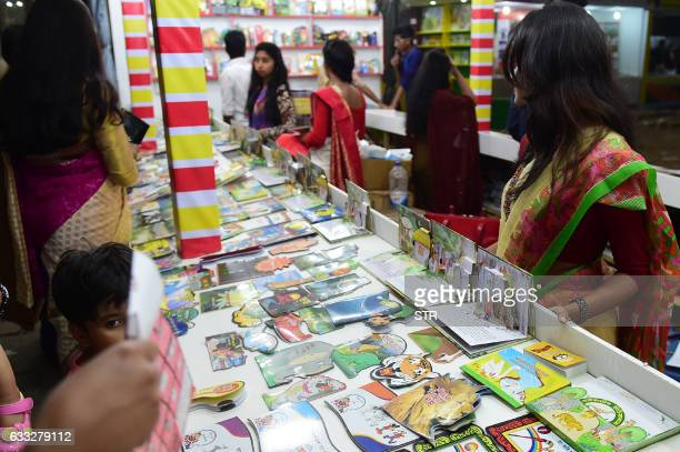 Bangladeshi shoppers brows books at a stall during the country's largest bookfair in Dhaka on February 1 2017 Bangladesh's largest book fair began in...