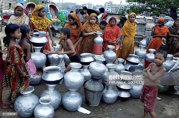 Bangladeshi slum dwellers stand with metal vessels as they await the arrival of water supplies on a street of Dkaha 03 September 2004 During the dry...
